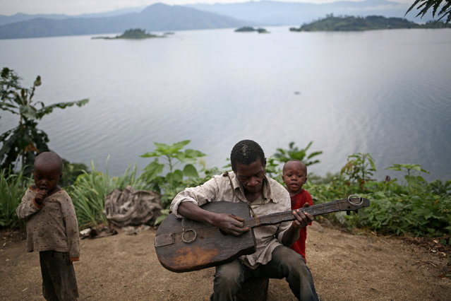 Mwenyezi, 36, plays a guitar at Kagorwa Pygmy camp on Idjwi island in the Democratic Republic of Congo, November 25, 2016. (Photo by Therese Di Campo/Reuters)