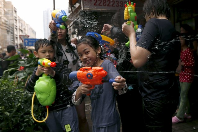 Children use water guns as they participate in a water fight during Songkran Festival celebrations at Kowloon City district, known as Little Thailand as there is large number of restaurants and shops run by Thais, April 12, 2015. (Photo by Tyrone Siu/Reuters)