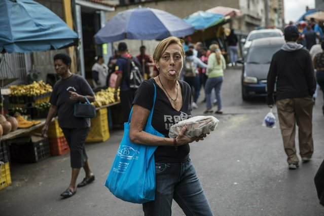 A woman sticks out her tongue as she shops at the Quinta Crespo street market in downtown Caracas, Venezuela, Saturday, January 26, 2019. The country's political showdown moves to the United Nations Saturday where a Security Council meeting called by the United States will pit backers of President Nicolas Maduro against the Trump administration and supporters of the country's self-declared interim leader Juan Guaido. (Photo by Rodrigo Abd/AP Photo)