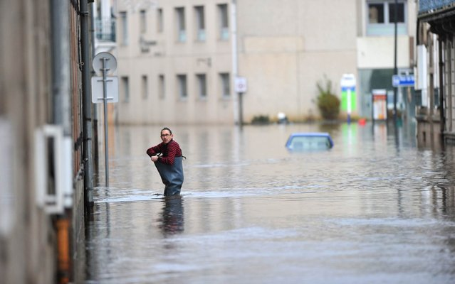 A man walks in a flooded street in Morlaix, Britanny, where the city center is under 1.4 metres (four feet) of water on December 24, 2013. Gale-force winds and pounding rain lashed Britain and France, killing at least two people, disrupting Christmas travel and leaving tens of thousands without power. A total of 240,000 French homes, mainly in the northwestern region of Brittany, were without electricity on Tuesday, according to power supplier ERDF. (Photo by Frank Perry/AFP Photo)