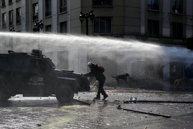 A protester blocks the way to a riot police vehicle during a demonstration against the government to demand changes in the education system at Santiago, April 16, 2015. (Photo by Ivan Alvarado/Reuters)