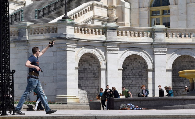 A policeman shows his badge while approaching a man who had just shot himself in front of the Capitol in Washington DC, as tourists react April 11, 2015. A man shot himself dead near the U.S. Capitol on Saturday, police said, sparking a temporary security lockdown at the complex on one of the busiest days for tourists in Washington. (Photo by Evan El-Amin/Reuters)
