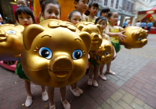 In this Friday, February 1, 2019, photo, Filipino-Chinese display piggy banks at the start of celebrations leading to next week's Lunar New Year in Chinatown, Manila, Philippines. This year is the Year of the Earth Pig on the Lunar calendar and is supposed to represent abundance, diligence and generosity. (Photo by Bullit Marquez/AP Photo)