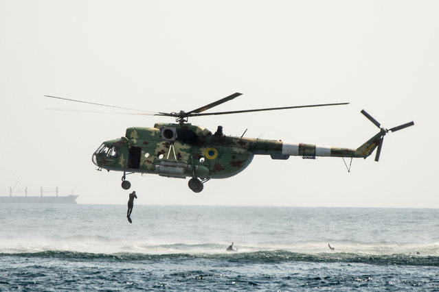A Ukrainian soldier jumps from a military helicopter during the  Independence Day celebrations in the Black Sea port of Odessa, Ukraine on August 24, 2021. (Photo by Mykhaylo Shtekel/Radio Free Europe/Radio Liberty)