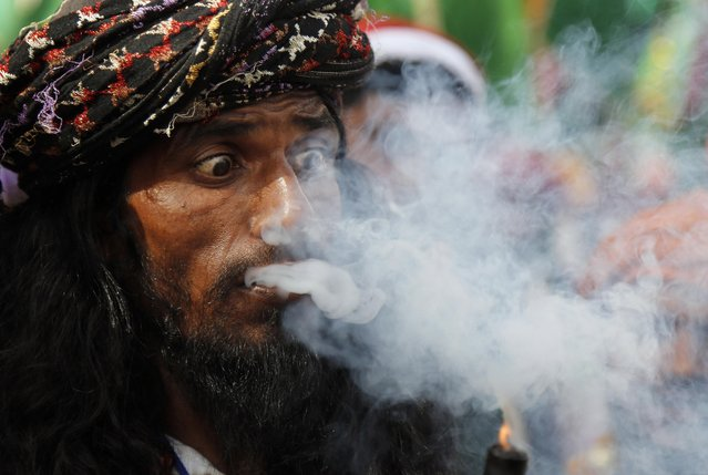 An Indian Muslim Sufi devotee smokes marijuana in a procession during the Urs festival at the shrine of Sufi saint Khwaja Moinuddin Chishti in Ajmer, India, Sunday, April 19, 2015. Thousands of Sufi devotees from different parts of India travel to the shrine for the annual festival, marking the death anniversary of the saint. (Photo by Deepak Sharma/AP Photo)