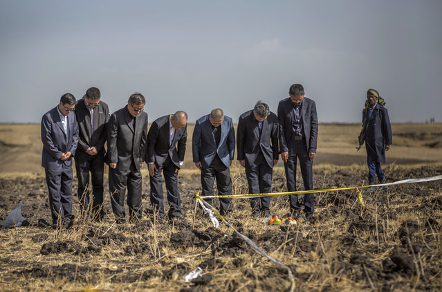 Officials from the Aviation Industry Corporation of China (AVIC) pray next to an offering of fruit, bread rolls, and a plastic container of Ethiopian Injera, a fermented sourdough flatbread, placed next to incense sticks, at the scene where the Ethiopian Airlines Boeing 737 Max 8 crashed shortly after takeoff on Sunday killing all 157 on board, near Bishoftu, or Debre Zeit, south of Addis Ababa, in Ethiopia Tuesday, March 12, 2019. Ethiopian Airlines had issued no new updates on the crash as of late afternoon Tuesday as families around the world waited for answers, while a global team of investigators began picking through the rural crash site. (Photo by Mulugeta Ayene/AP Photo)