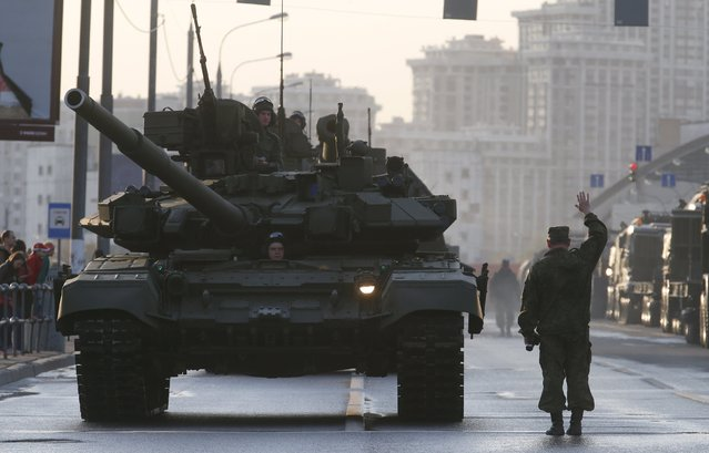 Russian servicemen are seen onboard a T-90 tank in a street before a rehearsal for the Victory Day parade in Moscow, Russia, April 29, 2015. (Photo by Maxim Zmeyev/Reuters)