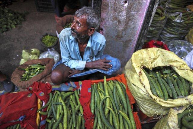 A farmer waits for customers at a wholesale vegetable market in Prayagraj, Uttar Pradesh state, India, Sunday, July 25, 2021. (Photo by Rajesh Kumar Singh/AP Photo)