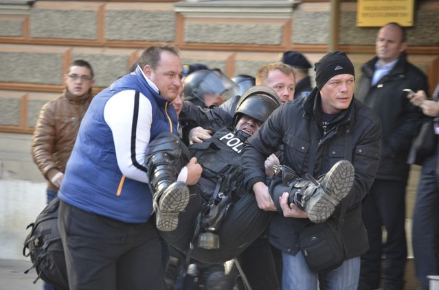 People help an injured policeman as anti-government protesters clash with police in Sarajevo February 7, 2014. (Photo by Reuters/Stringer)