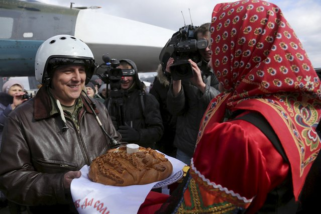 Participants welcome a Russian military pilot upon his return to a home airbase from Syria, during a traditional bread and salt ceremony in Buturlinovka in Voronezh region, Russia, March 15, 2016. (Photo by Olga Balashova/Reuters/Russian Ministry of Defence)