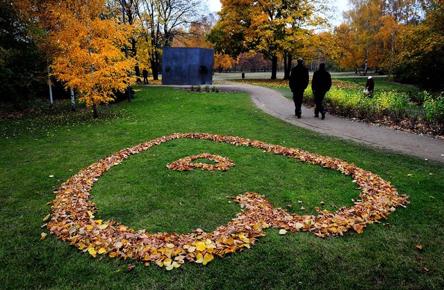 People walk past a heart made of autumnally colored leaves on the grass in Berlin's Tiergarten park. (Photo by Johannes Eisele/AFP Photo)