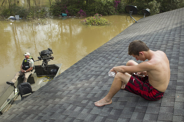 Trent Black sits on the roof of the home of Jamie Holden, Sr., surrounded by floodwaters from the Sabine River, Wednesday, March 16, 2016, in Deweyville, Texas. Swollen waterways have displaced thousands of people in flood-ravaged communities in Southeast Texas and floodwaters are forecast to rise even more. (Photo by Brett Coomer/Houston Chronicle via AP Photo)