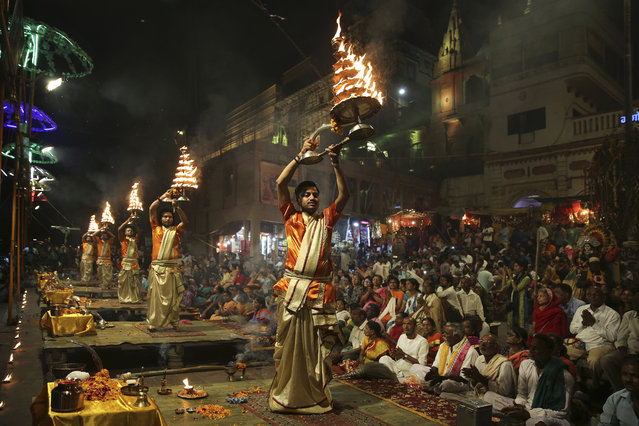 In this March 19, 2019, photo, devotees and tourists watch as Hindu priests perform daily rituals in reverence for river Ganges on its banks, in Varanasi, India. A project in the ancient Indian city of Varanasi dreamed up by Prime Minister Narendra Modi shows the master political marketer's penchant for symbolism as political strategy in elections that begin this month. (Photo by Altaf Qadri/AP Photo)
