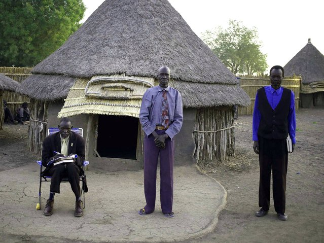 Men wait for Sunday mass near a church at a village in a rebel-controlled territory in Upper Nile State, South Sudan, February 9, 2014. (Photo by Goran Tomasevic/Reuters)