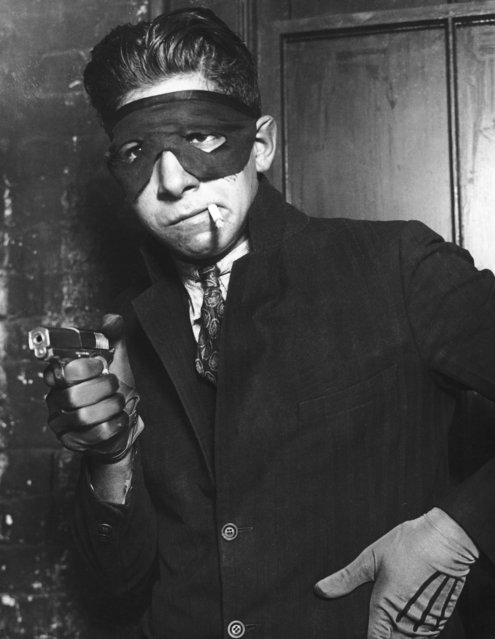 A young man posing as a masked gunman, circa 1930. (Photo by FPG/Hulton Archive/Getty Images)