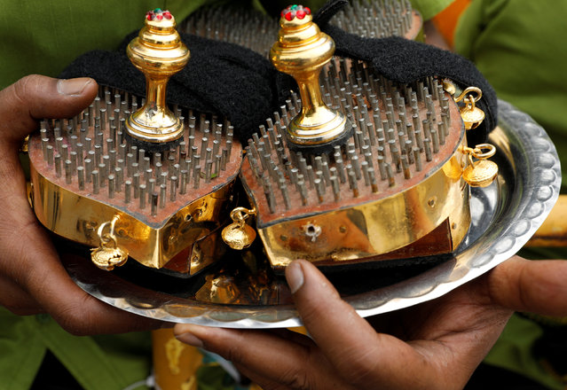A devotee carries a pair of clogs fashioned from nails during the Hindu festival of Thaipusam in Singapore February 9, 2017. (Photo by Edgar Su/Reuters)