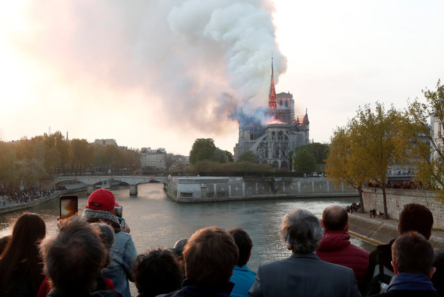 People watch from a bridge as smoke billows from Notre Dame Cathedral during a fire in Paris, France April 15, 2019. (Photo by Benoit Tessier/Reuters)