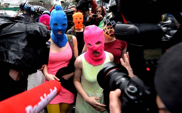 Wearing masks members of Russian punk group p*ssy Riot, Nadezhda Tolokonnikova (L) and Maria Alyokhina (R) speak to journalists while leaving the police station of Adler, near Sochi, on February 18, 2014 after her arrest earlier in the host city of the 2014 Winter Olympics. Tolokonnikova and Maria Alyokhina walked free after being questioned about an alleged theft from a hotel. (Photo by Andrej Isakovic/AFP Photo)