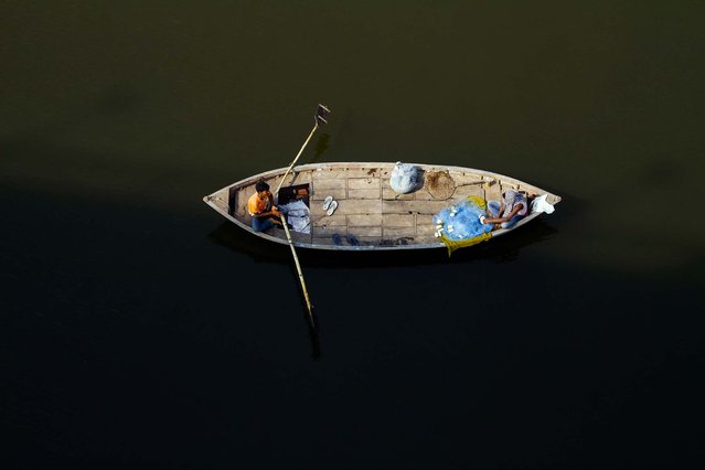 A fisherman rows a boat in the River Ganges in Allahabad, India. (Photo by Rajesh Kumar Singh/Associated Press)
