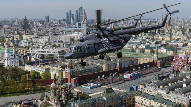 In this photo taken Thursday, May 7, 2015, a Russian airforce Mi-8 helicopter flies over the Moskva River, with the Kremlin in the background during a rehearsal of a V-Day military parade in Moscow, Russia. (Photo by Host photo agency/RIA Novosti Pool Photo via AP Photo)