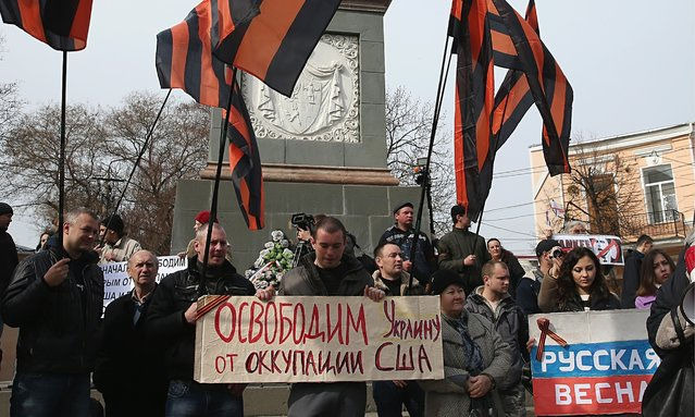 "Pro-Russian sympathizers, including one man holding a sign that reads: ""We will free Ukraine from American occupation"" and an elderly woman holding another that reads: ""Yankee Go Home!"", attend an anti-American rally hours after heavily-armed, unidentifed soldiers took up positions around the nearby Crimean Parliament on March 1, 2014 in Simferopol, Ukraine. (Photo by Sean Gallup/Getty Images)"