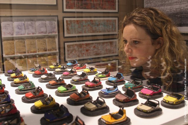 A Selfridges employee looks at an artwork by German artist Uwe Breckner at the Museum of Everything