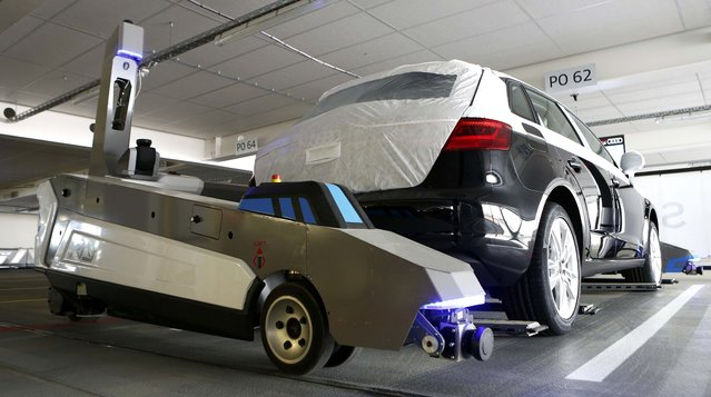 "Automated guided vehicle robot ""Ray"" lifts up an Audi car during a pilot project at the parking area of the Audi plant in Ingolstadt, Germany, May 13, 2015. The robot has been designed to help make work more efficient and more comfortable for employees, some whom walk up to eight kilometres a day, while coordinating the finished cars for the subsequent train transportation. (Photo by Michaela Rehle/Reuters)"