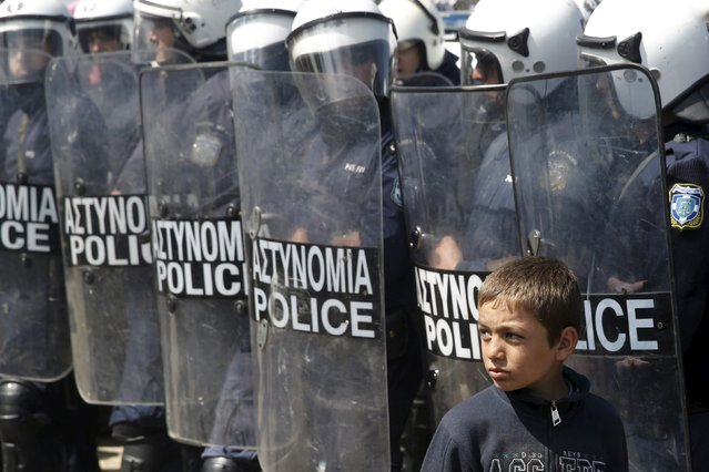 A child walks as Greek police officers stand guard after minor clashes occurred at a makeshift camp for migrants and refugees at the Greek-Macedonian border near the village of Idomeni, Greece, March 29, 2016. (Photo by Marko Djurica/Reuters)