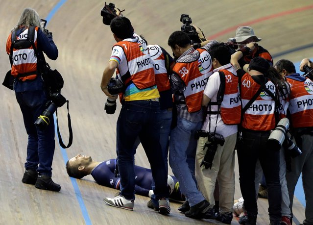 Photographers gather around France's Francois Pervis celebrating his gold medal in the men's sprint final at the Track Cycling World Championships in Cali, Colombia, Sunday, March 2, 2014. (Photo by Fernando Vergara/AP Photo)
