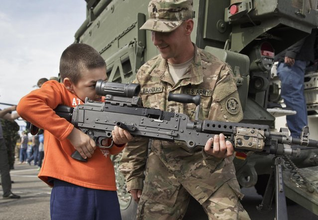 A U.S. Army serviceman helps a Romanian child look through the scope of a machine-gun in Ploiesti, Romania, Wednesday, May 13, 2015. Members of the US military took part in an exercise dubbed the Cavalry March, a drive from southern Romania to a training range in the central region of Transylvania, involving 400 servicemen and 80 armored combat vehicles. (Photo by Vadim Ghirda/AP Photo)