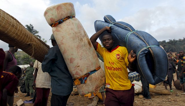 Burundian refugees carry their belongings as they board a boat on the shores of Lake Tanganyika in Kagunga village in Kigoma region in western Tanzania to Kigoma township, May 17, 2015. (Photo by Thomas Mukoya/Reuters)