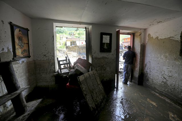 A resident stands at the entrance of his damaged house, after a landslide sent mud and water crashing onto homes close to the municipality of Salgar in Antioquia department, Colombia May 19, 2015. (Photo by Jose Miguel Gomez/Reuters)