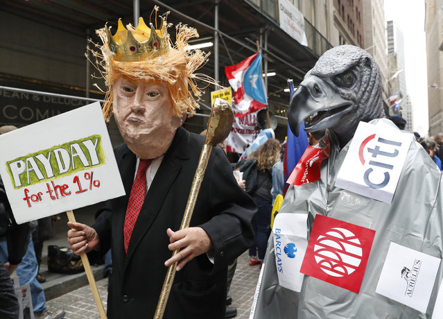 A man dressed as President Donald Trump holds a golf club as he stands beside a person dressed as a corporate vulture during a May Day rally in front of 40 Wall Street, a Trump-owned property, Wednesday, May 1, 2019, in New York. (Photo by Kathy Willens/AP Photo)