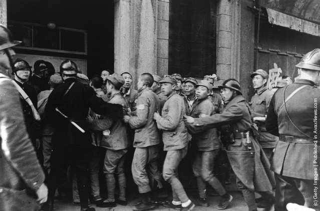 1937: French police try to control a crowd of Chinese soldiers seeking refuge in the French Concession after the fall of Nanto during the Sino-Japanese war