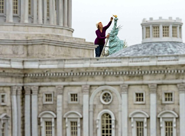 Model maker Helga Mueller restores the model of the Statue of Liberty of New York with gold foil behind a model of the Capitol of Washington in the landscape park Miniwelt (Miniworld) in Lichtenstein, eastern Germany, Wednesday, May 20, 2015. Miniwelt presents about 100 original and true-to detail buildings and technical facilities at a 1:25 scale. (Photo by Jens Meyer/AP Photo)