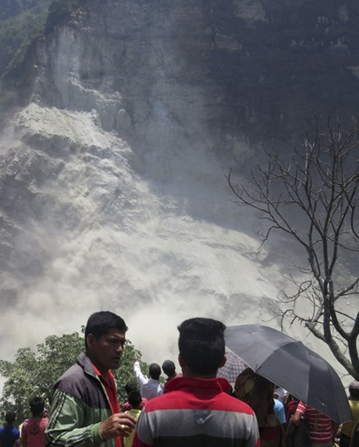People gather at the site of a landslide north of Beni Bazaar, Nepal, Sunday, May 24, 2015. Thousands of people fled villages and towns along a mountain river in northwest Nepal on Sunday after it was blocked by a landslide that could burst and cause flash floods, officials said. (Photo by M. B. Astha/AP Photo)