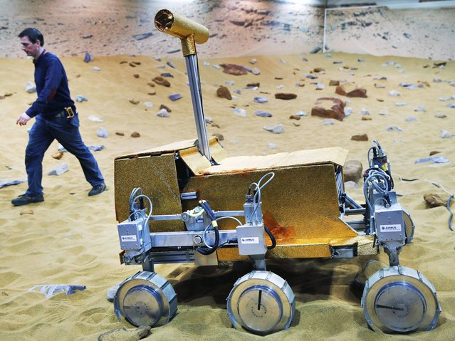 "Engineer Ben Nye walks past a robotic vehicle on the ""Mars Yard Test Area"", a testing ground for the robotic vehicles of the European Space Agency's ExoMars program scheduled for 2018, in Stevenage, England, Thursday, March 27, 2014. It looks like a giant sandbox – except the sand has a reddish tint and the ""toys"" on display are very expensive prototypes designed to withstand the rigors of landing on Mars. (Photo by Lefteris Pitarakis/AP Photo)"
