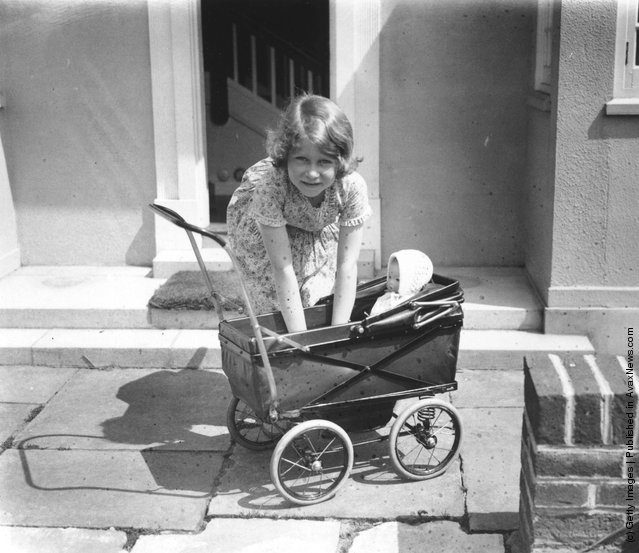 1933: Princess Elizabeth playing with a doll in a toy pram outside the Welsh House, a miniature house presented to Princess Elizabeth and Princess Margaret by the people of Wales in the grounds of the Royal Lodge, Windsor
