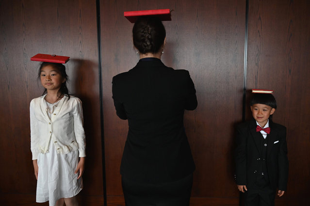 This picture taken on June 1, 2019 shows Miona Milakov (C) teaching children how to balance a book on their head during an etiquette and manners class in central Shanghai. (Photo by /Reuters)
