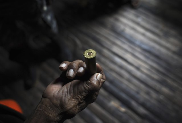 An Ashaninka Indian holds a shotgun cartridge he found on the grounds of the former government base called the Envira Front of Ethno-environmental Protection along the Envira river in Brazil's northwestern Acre state, March 14, 2014. (Photo by Lunae Parracho/Reuters)
