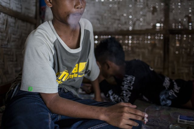 Candra (12), smokes at a kiosk on March 6, 2017 in Yogyakarta, Indonesia. (Photo by Ulet Ifansasti/Getty Images)
