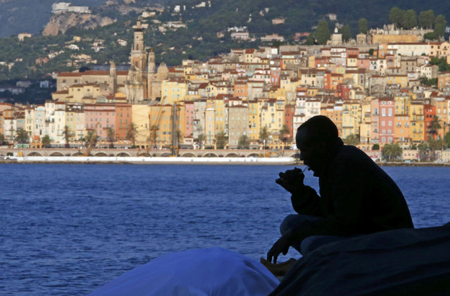 A migrant is silhouetted as he brushes his teeth on the rocks of the seawall at the Saint Ludovic border crossing on the Mediterranean Sea between Vintimille, Italy and Menton, France, June 17, 2015. Police on Tuesday began hauling away mostly African migrants from makeshift camps on the Italy-France border as European Union ministers met in Luxembourg to hash out plans to deal with the immigration crisis. The French city of menton is seen in the background.  REUTERS/Eric Gaillard
