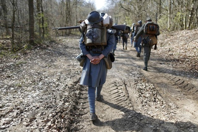 French (in blue) and German members of World War One historical associations take part in a 15-km (9-mile) walk through the national forest of Verdun, eastern France, March 29, 2014. (Photo by Charles Platiau/Reuters)