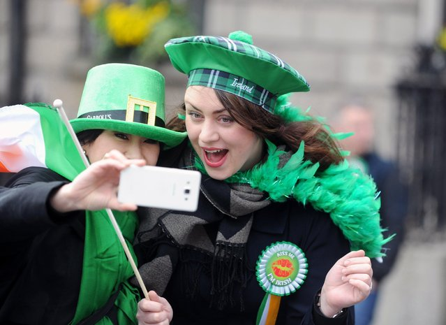 Two women take a selfie during the Saint Patrick's Day Parade in Dublin, Ireland, 17 March 2017. St. Patrick's Day is marked annually on 17 March to commemorate Saint Patrick, a patron saint of Ireland. (Photo by Aidan Crawley/EPA)