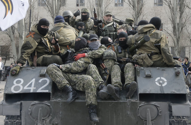 A combat vehicle with pro-Russian gunman on top runs through downtown Slovyansk on Wednesday, April 16, 2014. The troops on those vehicles wore green camouflage uniforms, had automatic weapons and grenade launchers and at least one had the St. George ribbon attached to his uniform, which has become a symbol of the pro-Russian insurgency in eastern Ukraine. (Photo by Efrem Lukatsky/AP Photo)