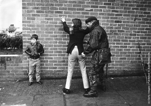 1971:  A British soldier searching a Belfast teenager