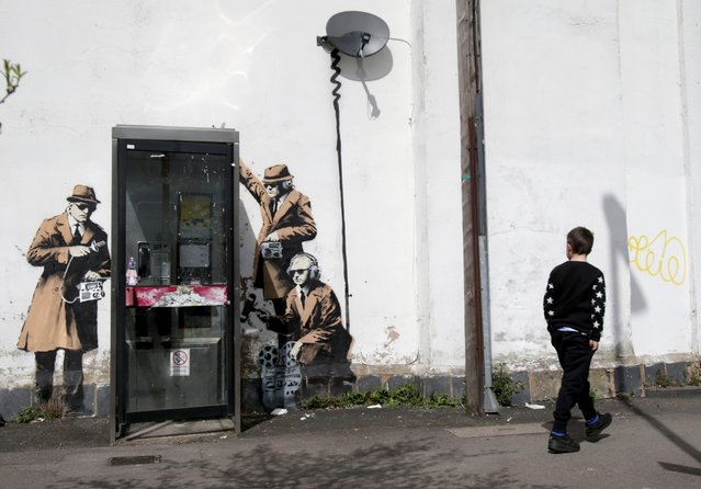 A boy walks past a piece of new graffiti street art, claimed to be by the secretive underground guerilla artist Banksy, which appeared on the side of a house in Cheltenham this weekend, on April 14, 2014 in Gloucestershire, England. The artwork, which shows three stencil figures listening into a conversation in an existing telephone box, is just a few miles away from Government Communications Headquaters (GCHQ), which is responsible for providing intelligence and information assurance to the British Government and Armed Forces. (Photo by Matt Cardy/Getty Images)