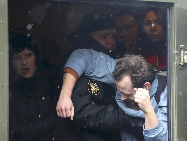 A law enforcement officer detains a man during a gathering, denouncing the new tax on those not in full-time employment and marking the 99th anniversary of the proclamation of the Belarussian People's Republic, in Minsk, Belarus, March 25, 2017. (Photo by Vasily Fedosenko/Reuters)