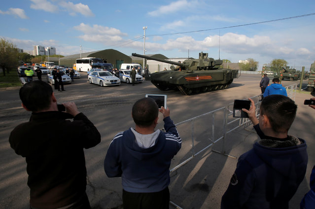 People take pictures of Russian T-14 tank with the Armata universal combat platform as it leaves a range to take part in a rehearsal for the Victory Day parade in Moscow, Russia, May 5, 2016. (Photo by Maxim Shemetov/Reuters)