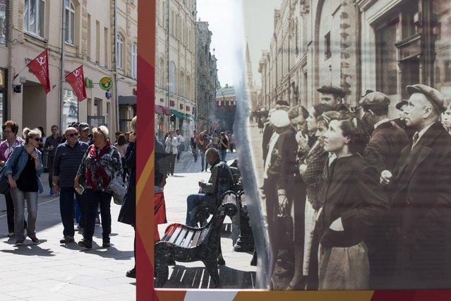 People walk by a poster showing a World War II era photo of people listening to news, and installed in preparation for Victory Day celebration just off Red Square in downtown Moscow, Russia, Friday, May 6, 2016. Victory Day, one of the most important holidays on Russia's calendar, commemorates the 1945 defeat of Nazi Germany in World War II. Victory Day is marked in Russia on May 9. (Photo by Alexander Zemlianichenko/AP Photo)
